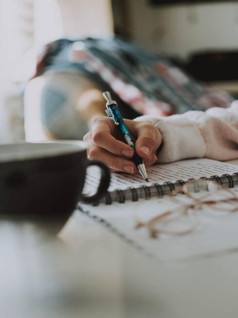 Vrouw schrijft in een notitieboekje