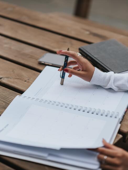 notitieblok met een potlood en een hand