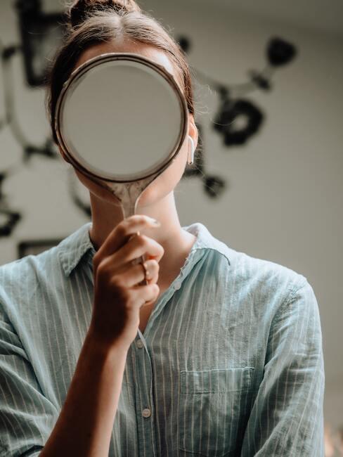 Vrouw houdt zichzelf een spiegel voor