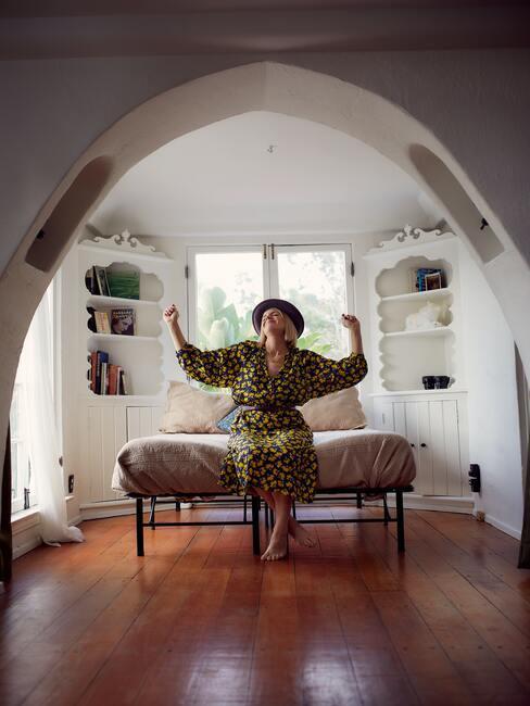 Vrouw zit op het randje van haar bed en doet een vreugdedansje