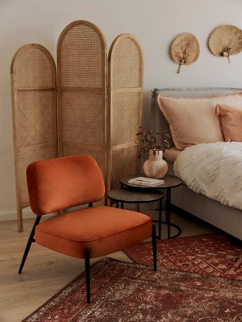 Rotan kamerscherm naast fluwelen fauteuil in oranje