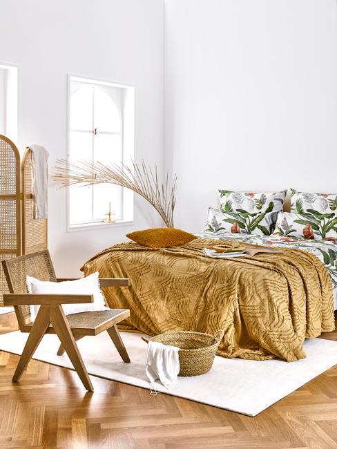 beddengoed in wit en met bladeren in groen naast een rotan kamerschem