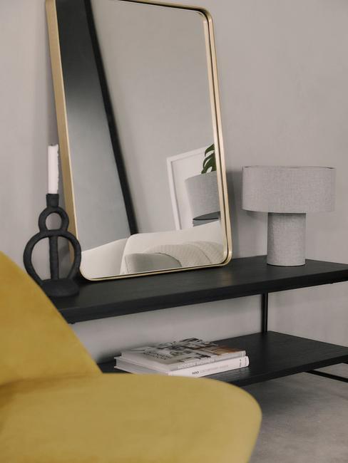 Zwarte metalen sideboard naast een fauteuil in geel