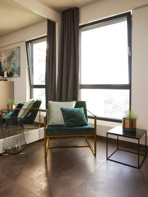 Fluwelen fauteuil in groen met sierkussens in de woonkamer