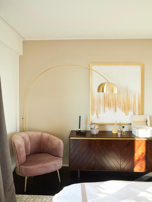 Fluwelen fauteuil in roze naast een massief houten dressoir en staande lamp in goud kleur