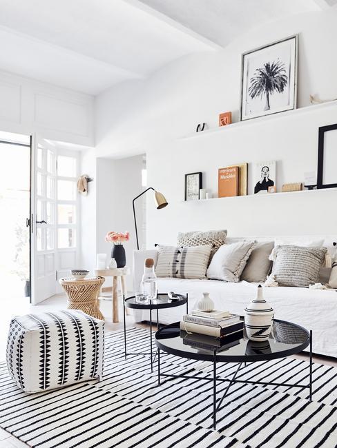 Woonkamer in lichte kleuren met fluwelen zitbank in grijs en sierkussens