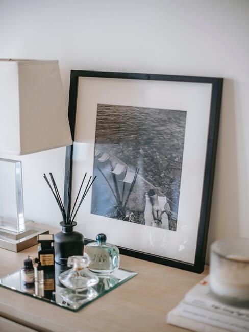 Fotolijstje en geurkaarsen op houten dressoir naast een tafellamp