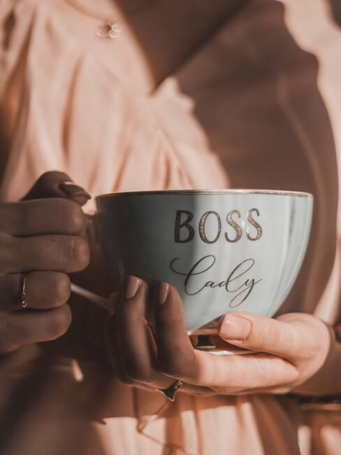Vrouw houdt mok vast met boss erop