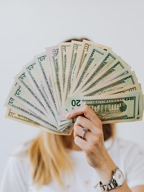 vrouw met briefgeld als een waaier in haar hand