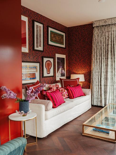 Huiskamer met rode muur, witte bank en veel rode en roze kussens