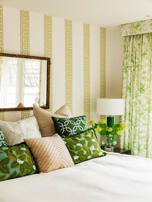 Slaapkamer met groen gestreept behang en veel gekleurde kussens op het bed