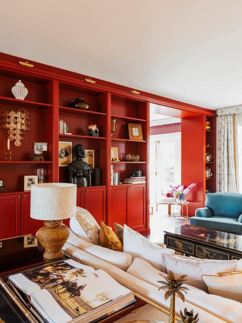 Huiskamer met rode boekenkast, grote natuurlijke lamp, witte bank met kussen en blauwe velvet lounge stoel