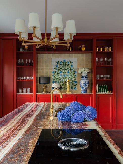 Moderne keuken met rode wand en marmeren keukenblad