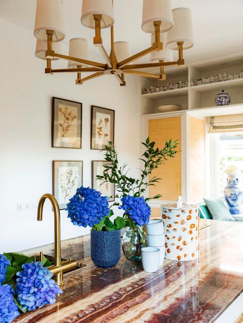 Moderne keuken met marmeren keukenblad, gouden hanglamp en gekleurde decoratieve items