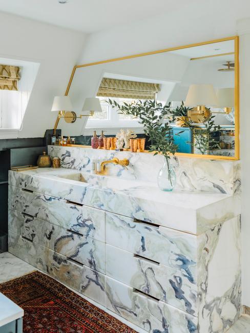 Marmere badkamer met een gouden langwerpige spiegel