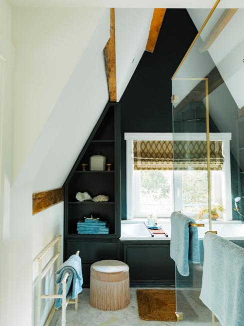 donkere badkamer met een balwue handdoek en houten wasmand