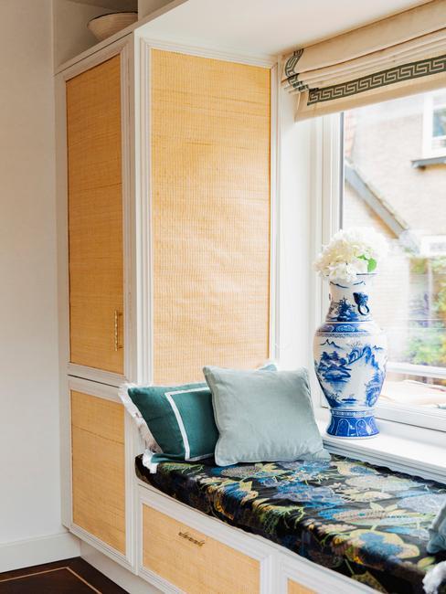 Raam met zitbank in de vensterbank met gekleurde kussens