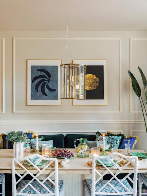 Kleurrijk gedekte eettafel en wand met kunst