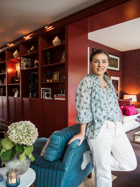 Petra leunt tegen blauwe lounge stoel in haar woonkamer