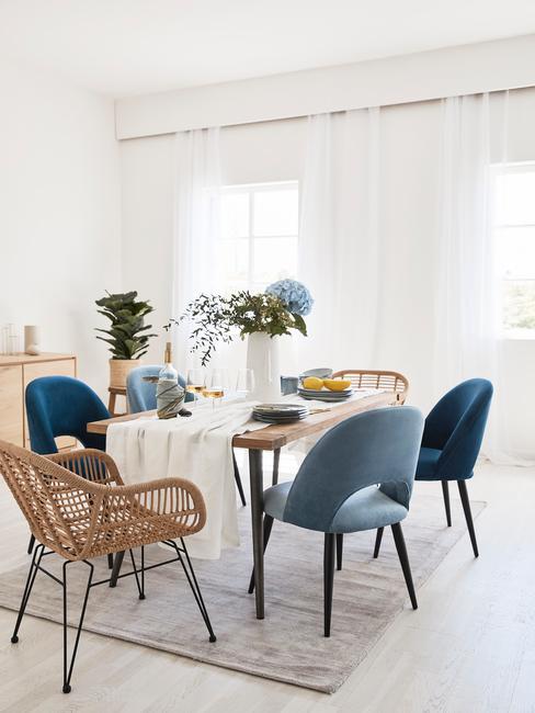 Woonkamer in lichte kleuren, met fluwelen fauteuil in blauw en rotan stoelen