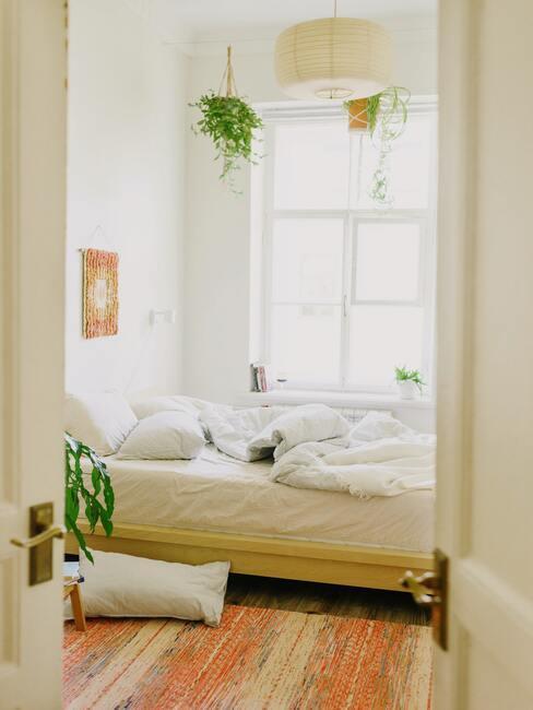 Slaapkamer met groot raam en witte bedlinnen