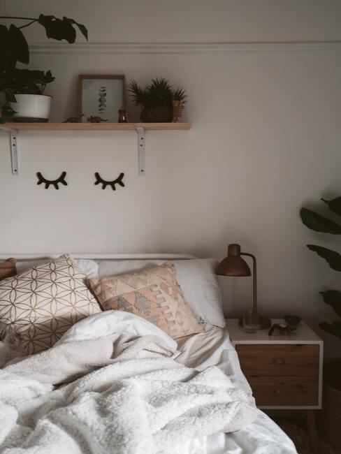 Slaapkamer in boho stijl met decoratieve objecten en bedlinnen in witte en roze tinten