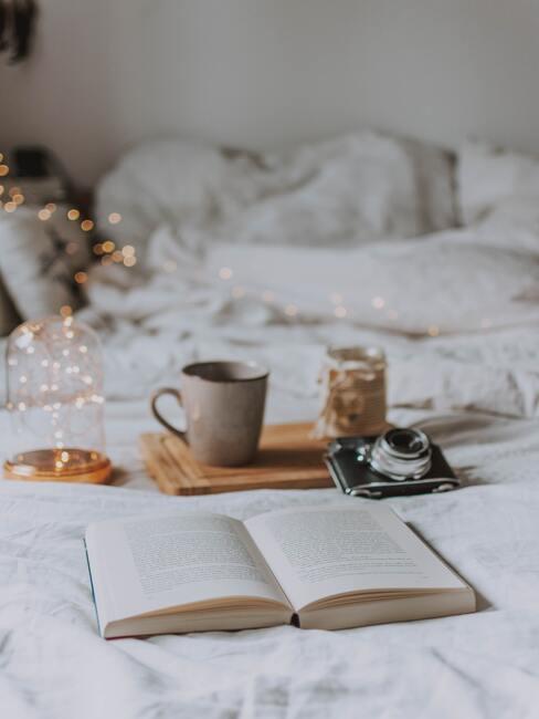 Boek en koffiekopje op bed