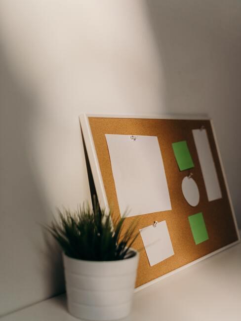 Belangrijke notitiesac over een kurkbord naast plantenpot in wit