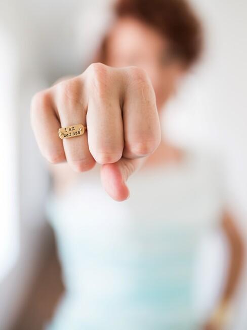 Vrouw met gebalde vuist en ring waar 'bad ass' op staat
