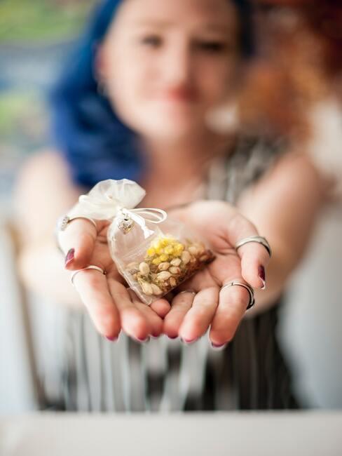 Close-up handen met geurzakje met gedrooged bloemen erin