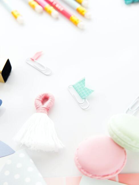 wit kwastje met roze hanger, macaroons in groen en roos, paperclips in blauw en roze