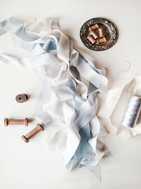 Close-up witte en blauwe linten, blauwe draad en lege garen klossen