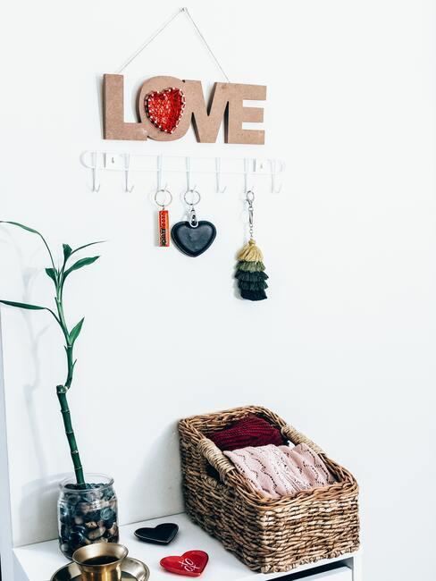 Close-up witte wand met love wandbord, wandkapstok met drie sleutelhangers, mand met sjaals en plant in pot