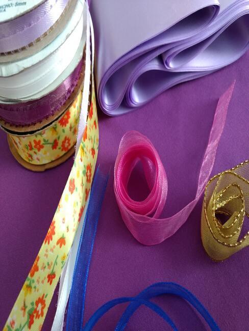 Linten in wit, goud, roze, paars, blauw en geel op paarse achtergrond