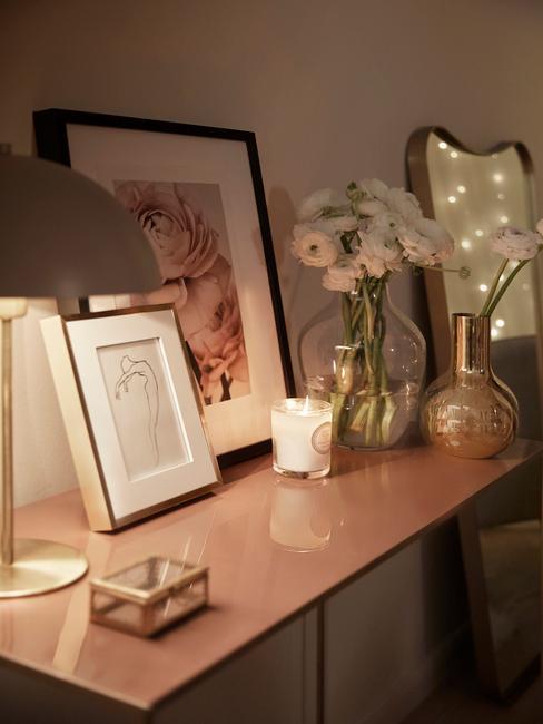 Roze tinten in de slaapkamer, kunst en nachtlampje op het dressoir