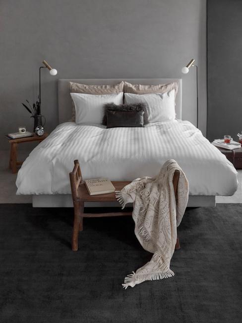 slaapkamer in betonlook met houten voetenbankje en natuurlijke materialen