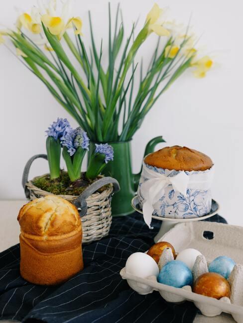 Paasgebakjes op tafel naast vaas met tulpen