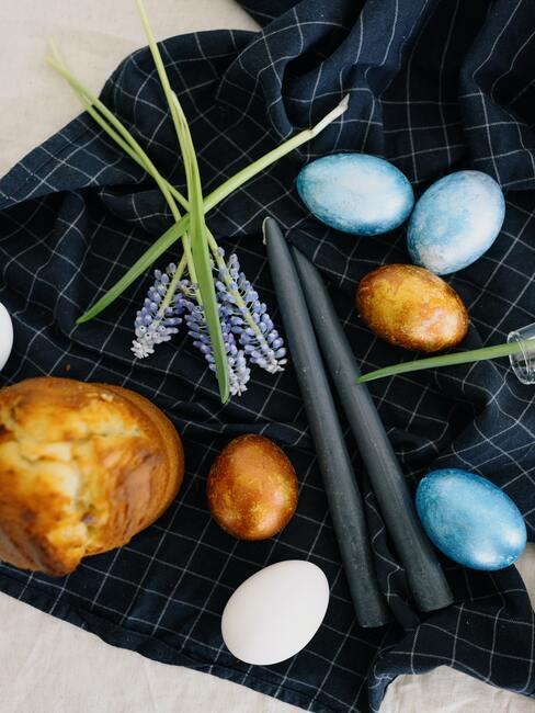 Paasgebakjes en eieren op tafel naast vaas met tulpen