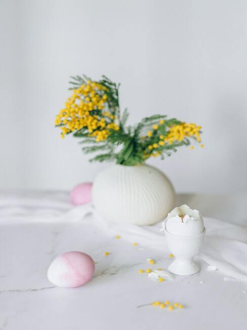Wit tafekleed op houten stoel, witte vaas met bloemen