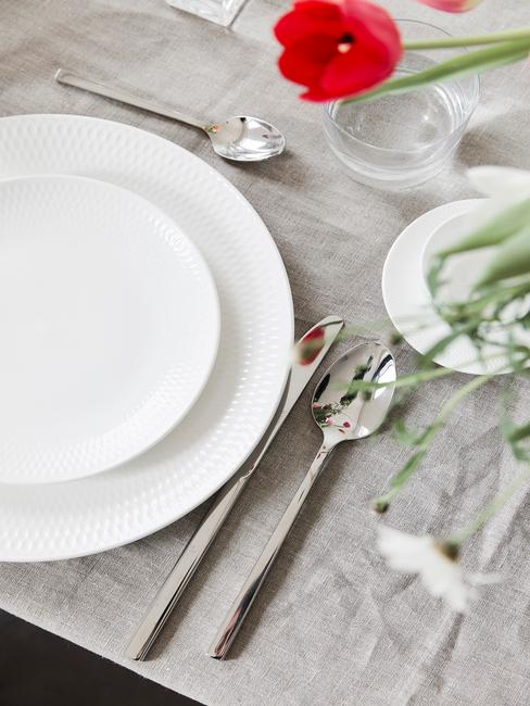 Witte serviesgoed en zilverkleurige bestekset