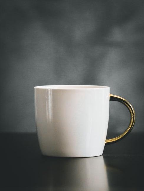 Wit koffiekopje met goudkleurige handvat