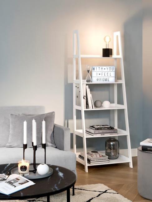 Witte boekenrek naast zitbank in grijs