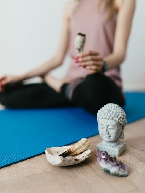 vrouw mediteert op een yogamat met een buddha op de voorgrond