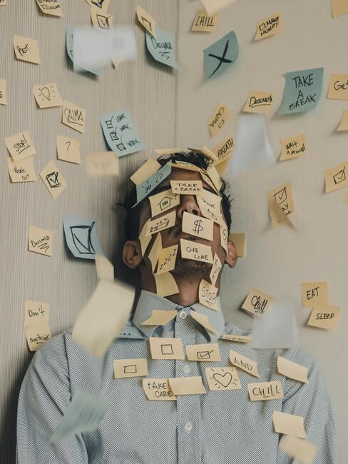 Man staat in een hoek van zijn kantoor met post-it's op zijn hoofd en op de muur geplakt