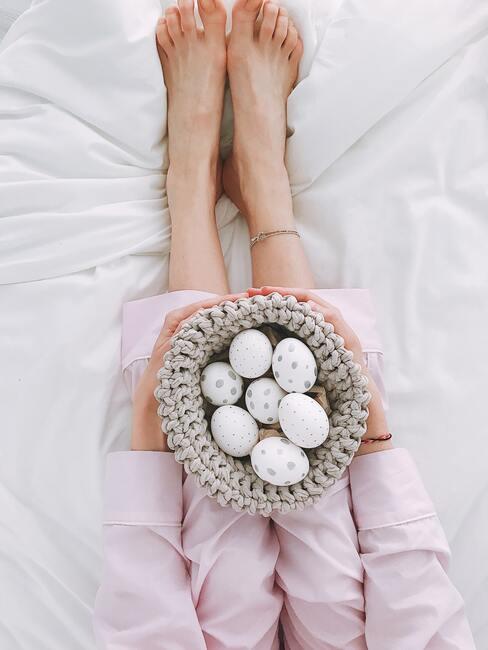 Vrouw in roze pyjama met witte eieren in een mand