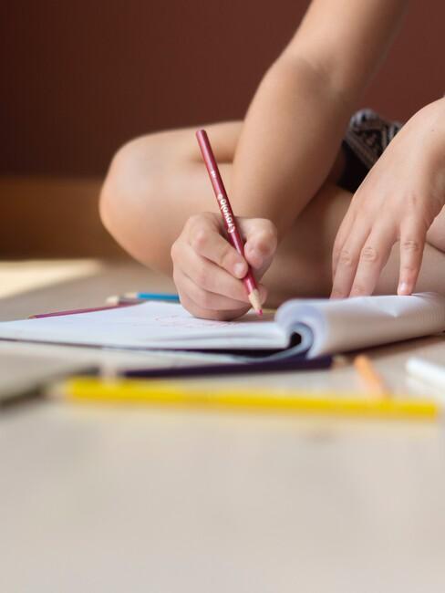 Kind tekent in een kleurboek