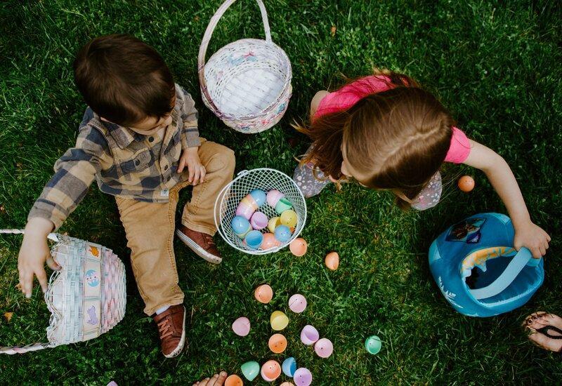Twee kinderen zitten in het gras met mandjes met paaseieren