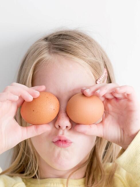 Klein meisje met twee eitjes voor haar gezicht