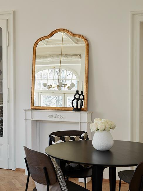 Barok spiegel op shouw met ronde zwarte tafel
