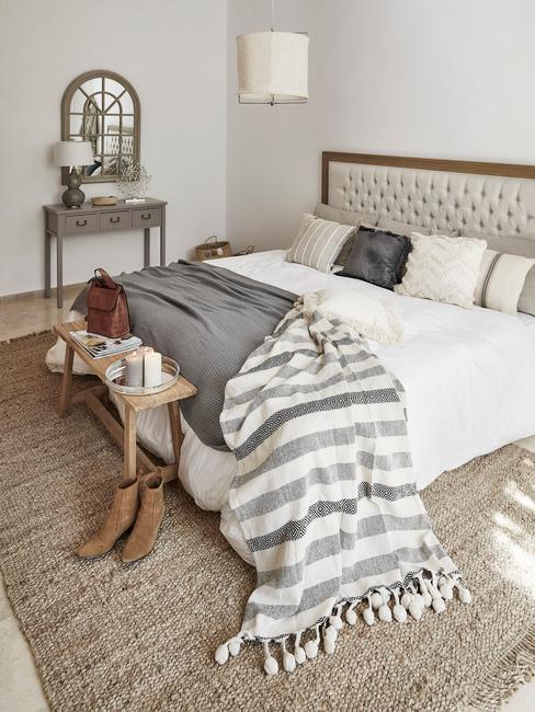 grijs bed met houten rand wit dekbed en grijze deken
